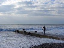 El deportista con el tablero que practica surf va a lo largo del embarcadero al mar Fotos de archivo