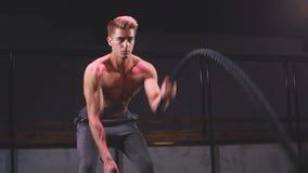 El deportista con las cuerdas de la batalla de la cuerda de la batalla ejercita en el gimnasio de la aptitud metrajes