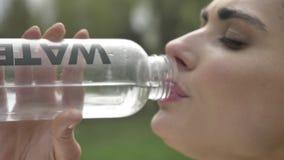 El deportista confiado joven de la muchacha bebe el agua afuera, forma de vida sana, concepto del deporte almacen de video