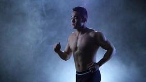 El deportista corre en fondo negro en estudio ahumado Carrocería muscular almacen de metraje de vídeo