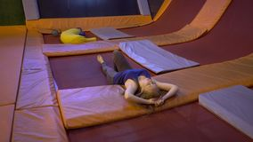 El deportista de la mujer joven cansó del salto en un trampolín en parque de la aptitud y de hacer exersice dentro metrajes