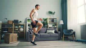 El deportista de sexo masculino activo está haciendo los ejercicios cardiios en casa que aumentan la elaboración de las piernas almacen de video