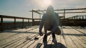 El deportista está apretando cordones en sus zapatillas de deporte juguetonas durante para resolverse al aire libre almacen de metraje de vídeo