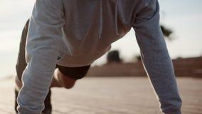 El deportista está haciendo flexiones de brazos en la calle durante mañana para resolverse almacen de metraje de vídeo