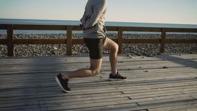 El deportista está haciendo posiciones en cuclillas con estocadas al aire libre el mañana para resolverse almacen de video