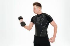 El deportista fuerte hermoso hace ejercicios de los deportes con pesa de gimnasia Imagen de archivo