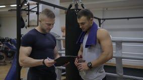 El deportista joven está discutiendo entrenando a resultados su instructor en el gimnasio almacen de metraje de vídeo