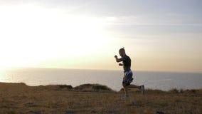 El deportista joven realiza tirones engaña por el mar contra el cielo en posluminiscencia almacen de video