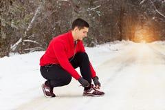 El deportista joven y hermoso en suéter rojo ata los cordones de sus zapatillas de deporte Actividad al aire libre imagen de archivo