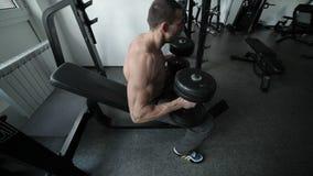 El deportista presiona pesas de gimnasia pesadas almacen de video