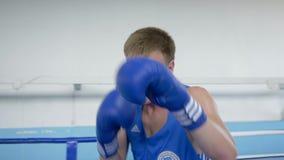 El deportista resuelve la técnica de las huelgas del boxeador en el entrenamiento antes de partido en el anillo, bate el primer d almacen de video