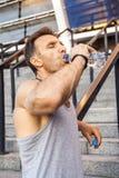 El deportista sediento toma un resto y un agua potable después de correr imagen de archivo