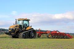 El desafiador MT765C siguió el tractor agrícola y al cultivador imagen de archivo