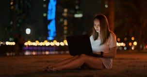 El desarrollador de la mujer se sienta en el parque en la noche en la ciudad y escribe el código que mira la pantalla del ordenad metrajes