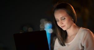 El desarrollador de la mujer se sienta en el parque en la noche en la ciudad y escribe el c?digo que mira la pantalla del ordenad metrajes