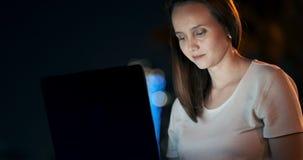 El desarrollador de la mujer se sienta en el parque en la noche en la ciudad y escribe el c?digo que mira la pantalla del ordenad almacen de metraje de vídeo