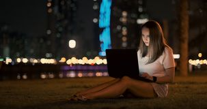 El desarrollador de la mujer se sienta en el parque en la noche en la ciudad y escribe el c?digo que mira la pantalla del ordenad almacen de video