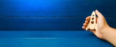 El desarrollo del espacio exterior Fondo de madera azul Entrenamiento, juego Concepto disponible de Rocket La mano sostiene un co fotografía de archivo