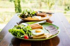 El desayuno consiste eeg, ensalada, pan, tocino y salchicha Fotografía de archivo libre de regalías