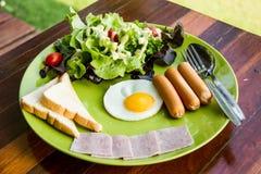 El desayuno consiste eeg, ensalada, pan, tocino y salchicha Imagenes de archivo