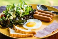 El desayuno consiste eeg, ensalada, pan, tocino y salchicha Imágenes de archivo libres de regalías