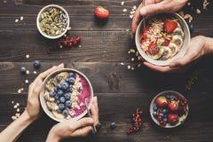 El desayuno de Helthy da sostener los cuencos deliciosos del smoothie con las frutas, las bayas y las semillas en el fondo de mad imagenes de archivo