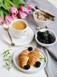 El desayuno de la mañana con la taza de café, de cruasanes, de bayas frescas y de rosa florece tulipanes Imágenes de archivo libres de regalías