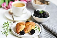 El desayuno de la mañana con la taza de café, de cruasanes, de bayas frescas y de rosa florece tulipanes Imagen de archivo libre de regalías