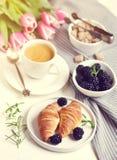 El desayuno de la mañana con la taza de café, de cruasanes, de bayas frescas y de rosa florece tulipanes Fotografía de archivo libre de regalías