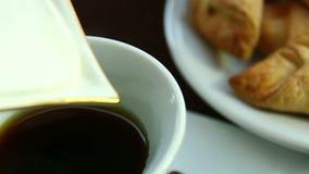 El desayuno de la mañana en la tabla es granos y galletas de café La crema azotada se vierte en una taza de café blanca Primer almacen de metraje de vídeo