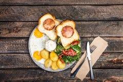 El desayuno delicioso grande con los huevos fritos, las patatas fritas, ensalada fresca, jamón del pollo en el pan y salsa cremos fotos de archivo