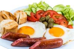 El desayuno el huevo frito que las verduras frescas frieron las salchichas y las aceitunas en una placa blanca fotografía de archivo libre de regalías
