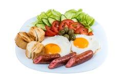 El desayuno el huevo frito que las verduras frescas frieron las salchichas y las aceitunas en una placa blanca foto de archivo libre de regalías
