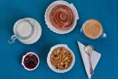 El desayuno ligero consiste en muesli, el bollo, el atasco, y el café en la aguamarina Imagen de archivo