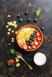 El desayuno-maíz fresco forma escamas con leche, fresas y arándanos en un fondo oscuro Visión desde arriba, endecha plana fotos de archivo libres de regalías