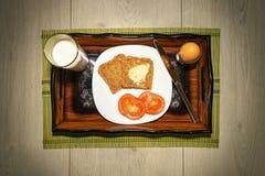 El desayuno simple con los huevos, la leche, el tomate y el pan tostado sirvió agradable en la bandeja de madera del vintage fotografía de archivo libre de regalías