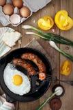 El desayuno sirvió con los huevos revueltos, las salchichas fritas, los tomates amarillos y las cebollas verdes Fotografía de archivo