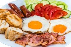 El desayuno el tocino frito de las verduras frescas del huevo frito, las salchichas fritas y las aceitunas en una placa blanca fotos de archivo libres de regalías