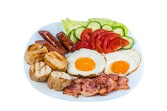 El desayuno el tocino frito de las verduras frescas del huevo frito, las salchichas fritas y las aceitunas en una placa blanca fotografía de archivo