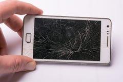 El descenso de Smartphone al piso y la pantalla dañan quebrado en el fondo blanco Imágenes de archivo libres de regalías