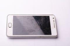 El descenso de Smartphone al piso y la pantalla dañan quebrado en el fondo blanco Fotos de archivo