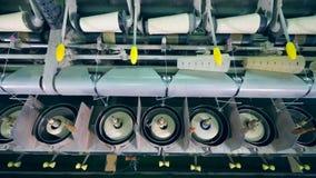 El desenrollar mecánico de carretes con los hilos blancos Materia textil, equipo que hace punto en una fábrica de la producción metrajes