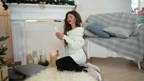 El deseo del ` s del Año Nuevo, la muchacha con una vela en su mano, sentándose en la chimenea y el árbol de navidad, piensa, hac almacen de metraje de vídeo