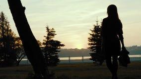 El desfiladero de la muchacha en el parque, lanzando hacia fuera una bufanda durante un paseo 4K almacen de video