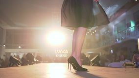 El desfile de moda, las piernas hermosas en zapatos de tacón alto negros toma vueltas en el podio en la presentación de la nueva  metrajes