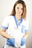 El desgastar del doctor o de la enfermera de la mujer joven friega imágenes de archivo libres de regalías