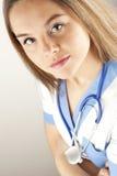 El desgastar del doctor o de la enfermera de la mujer joven friega Imagenes de archivo