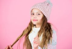 El desgaste de la muchacha hizo punto el fondo del rosa del sombrero Prevenga el daño del pelo del invierno Extremidades del cuid imagenes de archivo