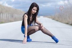 El desgaste de mujer una falda azul y medias negras presenta en el camino abierto Foto de archivo libre de regalías