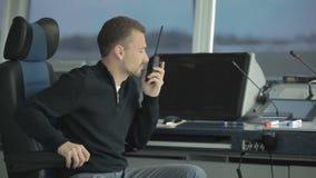 El despachador aprende sobre incidente en aeropuerto a través de la radio portátil almacen de metraje de vídeo